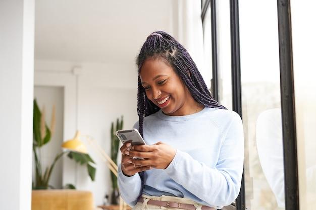 Jonge afro-amerikaanse vrouw die een slimme telefoon thuis bij het raam gebruikt