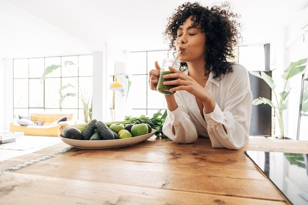 Jonge afro-amerikaanse vrouw die groen sap drinkt met herbruikbaar bamboestro in loft-appartement. huisconcept. gezond levensstijlconcept. ruimte kopiëren