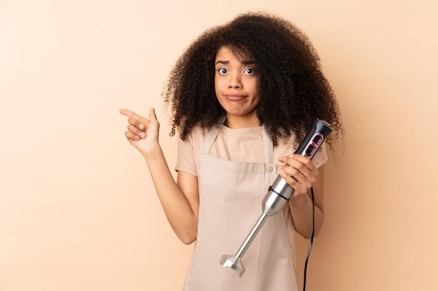 Jonge afro-amerikaanse vrouw die handmixer gebruikt die op beige muur wordt geïsoleerd die aan de lateralen richt die twijfels hebben
