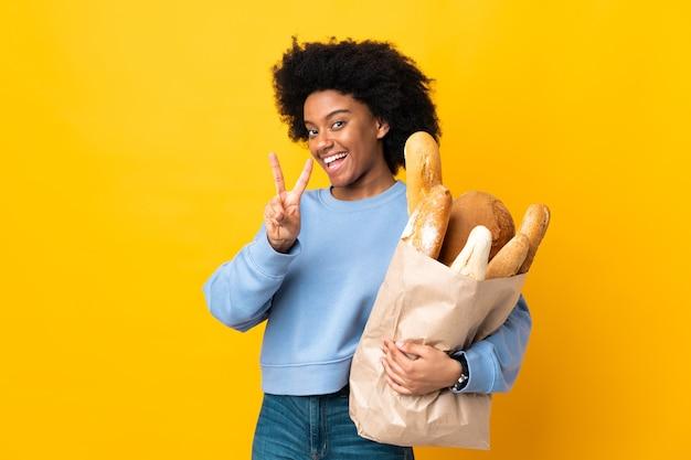 Jonge afro-amerikaanse vrouw die iets brood koopt dat op geel wordt geïsoleerd dat en overwinningsteken glimlacht toont