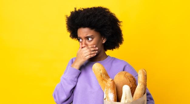 Jonge afro-amerikaanse vrouw die iets brood koopt dat op geel wordt geïsoleerd dat mond behandelt en naar de kant kijkt