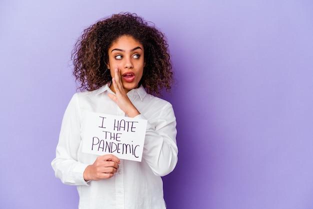 Jonge afro-amerikaanse vrouw die ik haat pandemisch plakkaat geïsoleerd op paarse achtergrond vasthoudt, zegt een geheim heet remnieuws en kijkt opzij