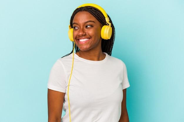 Jonge afro-amerikaanse vrouw die naar muziek luistert die op een blauwe achtergrond is geïsoleerd, kijkt glimlachend, vrolijk en aangenaam opzij.