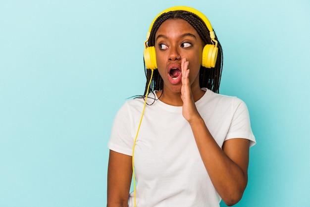 Jonge afro-amerikaanse vrouw die naar muziek luistert die op een blauwe achtergrond is geïsoleerd, zegt een geheim heet remnieuws en kijkt opzij