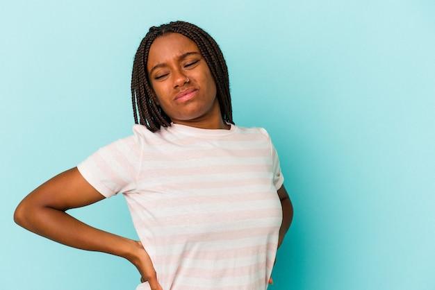 Jonge afro-amerikaanse vrouw die op blauwe achtergrond wordt geïsoleerd die aan rugpijn lijdt.