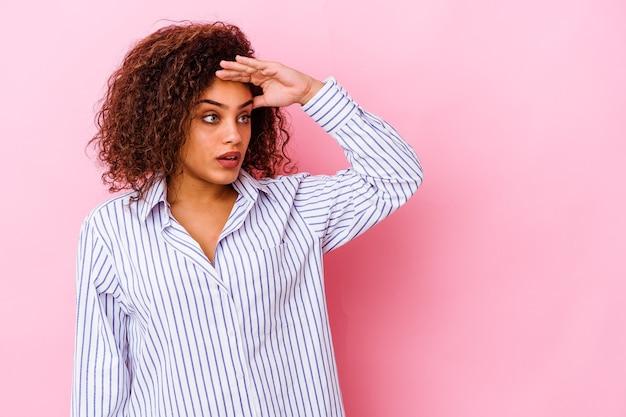 Jonge afro-amerikaanse vrouw die op roze achtergrond wordt geïsoleerd die ver weg kijkt die hand op voorhoofd houdt.