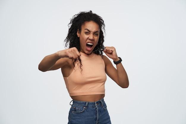 Jonge afro-amerikaanse vrouw die over een witte achtergrond staat als bokser
