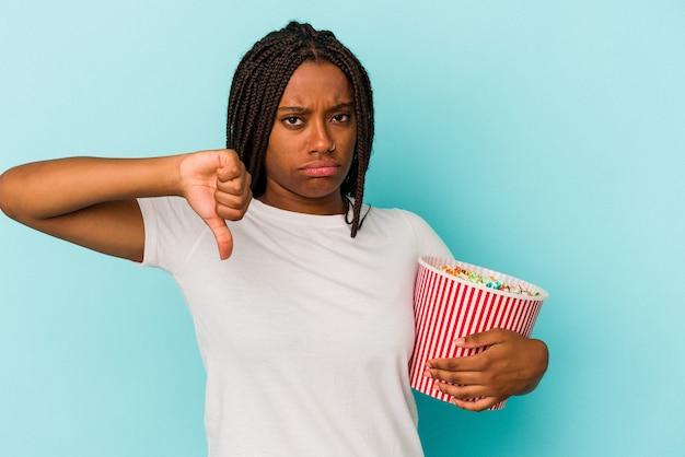Jonge afro-amerikaanse vrouw die popcorn eet geïsoleerd op een blauwe achtergrond met een afkeer gebaar, duim omlaag. onenigheid begrip.