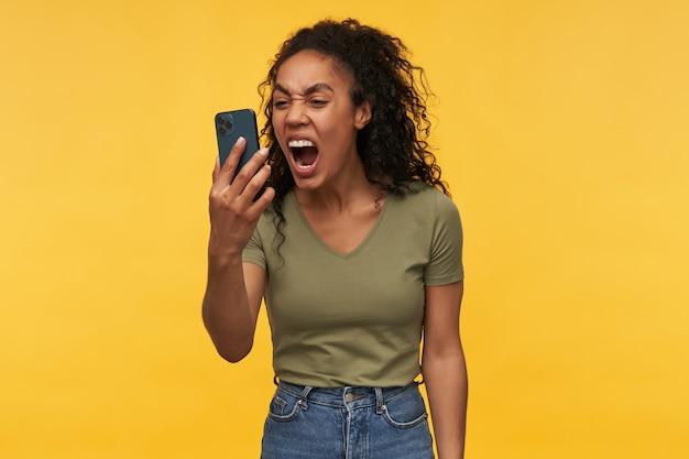 Jonge afro-amerikaanse vrouw draagt een groen t-shirt, heeft ruzie met iemand en schreeuwt in de telefoon