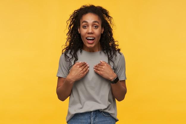 Jonge afro-amerikaanse vrouw, draagt grijs t-shirt en spijkerbroek, wijst met beide handen naar zichzelf met geopende mond