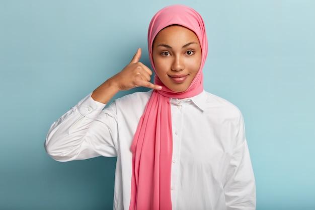 Jonge afro-amerikaanse vrouw draagt hijab, maakt bel me gebaar, vormt handen als telefoon in de buurt van oor, heeft tevreden gelaatsuitdrukking, praat op afstand met iemand