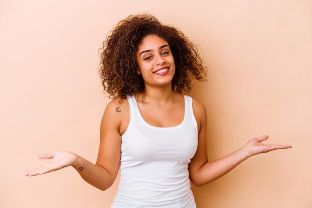 Jonge afro-amerikaanse vrouw geïsoleerd op beige achtergrond met een welkome uitdrukking.
