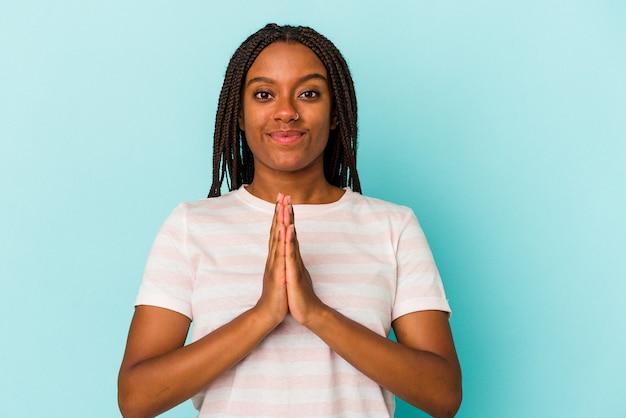 Jonge afro-amerikaanse vrouw geïsoleerd op blauwe achtergrond bidden, tonen toewijding, religieuze persoon op zoek naar goddelijke inspiratie.