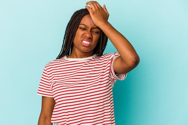 Jonge afro-amerikaanse vrouw geïsoleerd op blauwe achtergrond iets vergeten, voorhoofd met palm slaan en ogen sluiten.