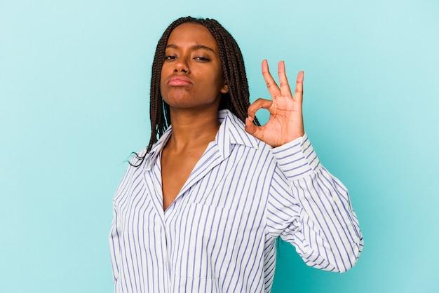 Jonge afro-amerikaanse vrouw geïsoleerd op blauwe achtergrond knipoogt en houdt een goed gebaar met de hand.