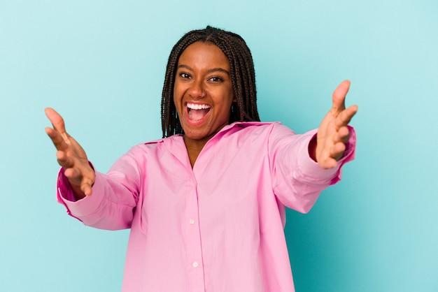 Jonge afro-amerikaanse vrouw geïsoleerd op blauwe achtergrond voelt zich zelfverzekerd en geeft een knuffel aan de camera.