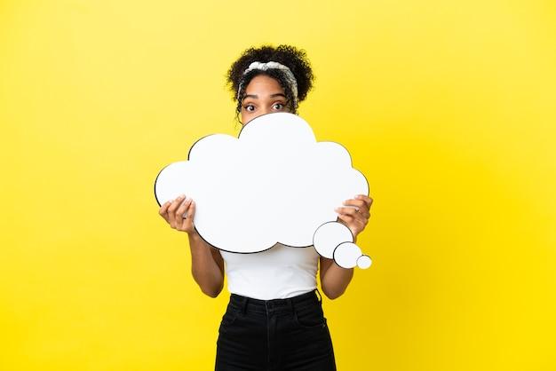 Jonge afro-amerikaanse vrouw geïsoleerd op een gele achtergrond die een denkende tekstballon vasthoudt en zich erachter verschuilt
