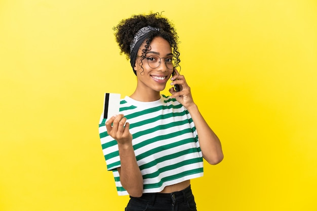 Jonge afro-amerikaanse vrouw geïsoleerd op een gele achtergrond die een gesprek voert met de mobiele telefoon en een creditcard vasthoudt
