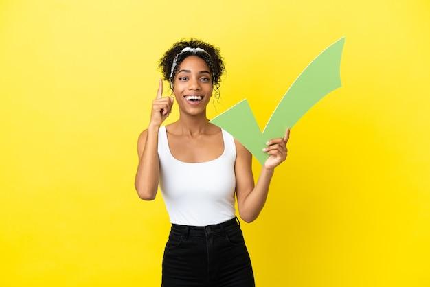 Jonge afro-amerikaanse vrouw geïsoleerd op een gele achtergrond met een vinkje en omhoog gericht