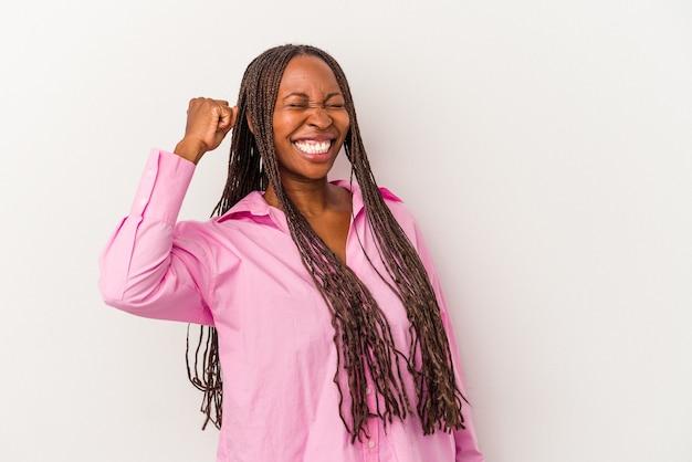 Jonge afro-amerikaanse vrouw geïsoleerd op een witte achtergrond die een overwinning, passie en enthousiasme, gelukkige uitdrukking viert.