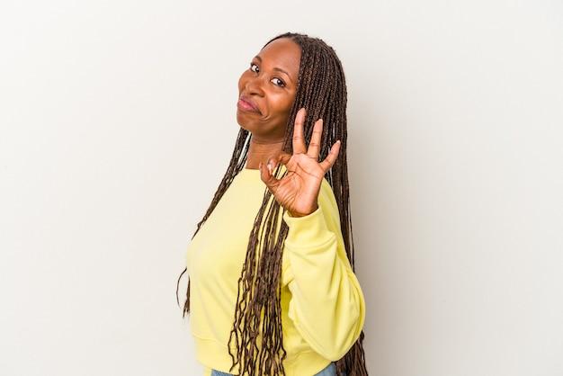 Jonge afro-amerikaanse vrouw geïsoleerd op een witte achtergrond knipoogt een oog en houdt een goed gebaar met de hand.
