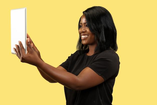 Jonge afro-amerikaanse vrouw geïsoleerd op geel, gezichtsuitdrukking