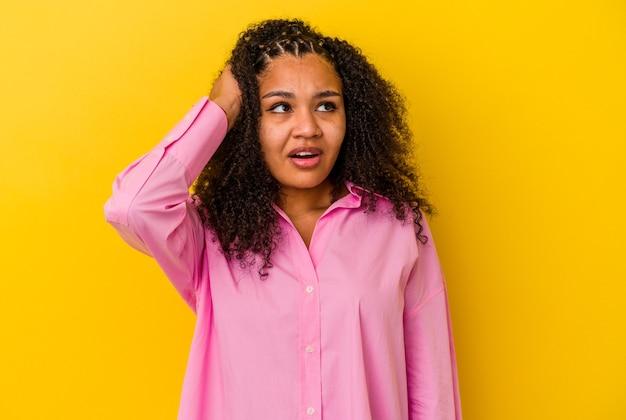 Jonge afro-amerikaanse vrouw geïsoleerd op gele achtergrond geschokt, ze heeft belangrijke ontmoeting onthouden.