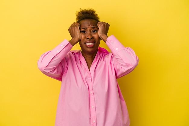 Jonge afro-amerikaanse vrouw geïsoleerd op gele achtergrond huilen, ongelukkig met iets, pijn en verwarring concept.
