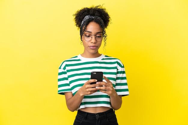 Jonge afro-amerikaanse vrouw geïsoleerd op gele achtergrond met behulp van mobiele telefoon