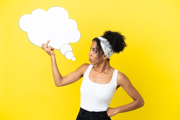 Jonge afro-amerikaanse vrouw geïsoleerd op gele achtergrond met een denkende tekstballon