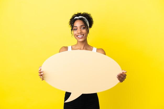 Jonge afro-amerikaanse vrouw geïsoleerd op gele achtergrond met een lege tekstballon