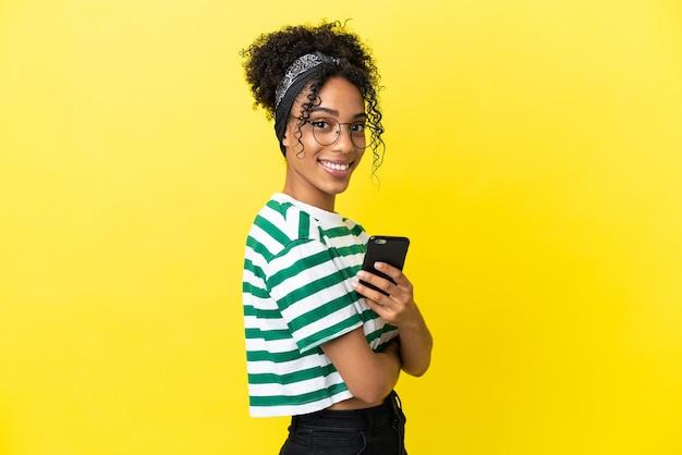 Jonge afro-amerikaanse vrouw geïsoleerd op gele achtergrond met een mobiele telefoon en met gekruiste armen