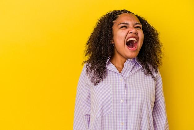 Jonge afro-amerikaanse vrouw geïsoleerd op gele achtergrond schreeuwen erg boos, woede concept, gefrustreerd.