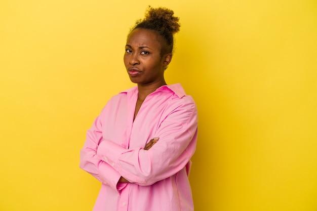 Jonge afro-amerikaanse vrouw geïsoleerd op gele achtergrond verdacht, onzeker, u onderzoeken.