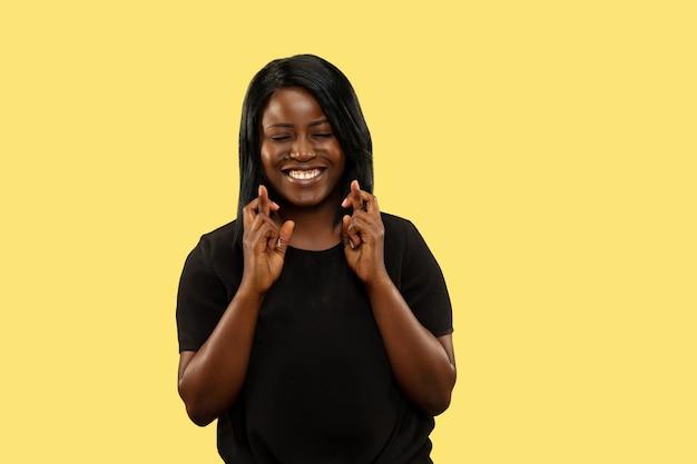 Jonge afro-amerikaanse vrouw geïsoleerd op gele studio achtergrond, gezichtsuitdrukking. mooi vrouwelijk portret van halve lengte. concept van menselijke emoties, gezichtsuitdrukking. hoop op veel geluk.