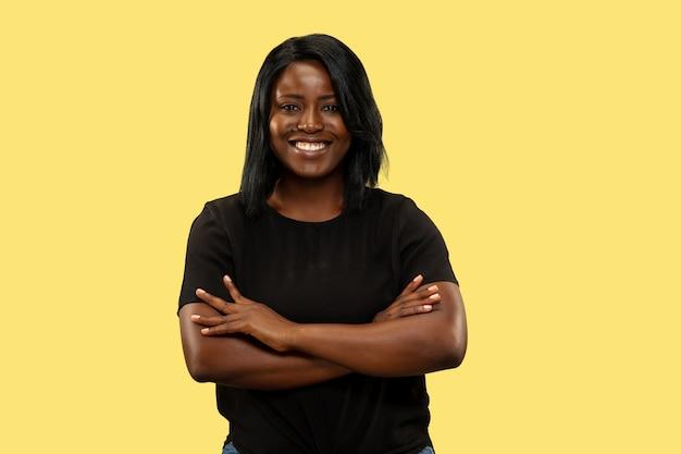 Jonge afro-amerikaanse vrouw geïsoleerd op gele studio achtergrond, gezichtsuitdrukking. mooi vrouwelijk portret van halve lengte. concept van menselijke emoties, gezichtsuitdrukking. staande kruisende handen.