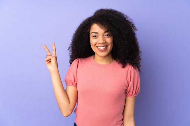 Jonge afro-amerikaanse vrouw geïsoleerd op paars glimlachend en overwinningsteken tonen