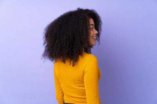 Jonge afro-amerikaanse vrouw geïsoleerd op paars in achterste positie en op zoek kant