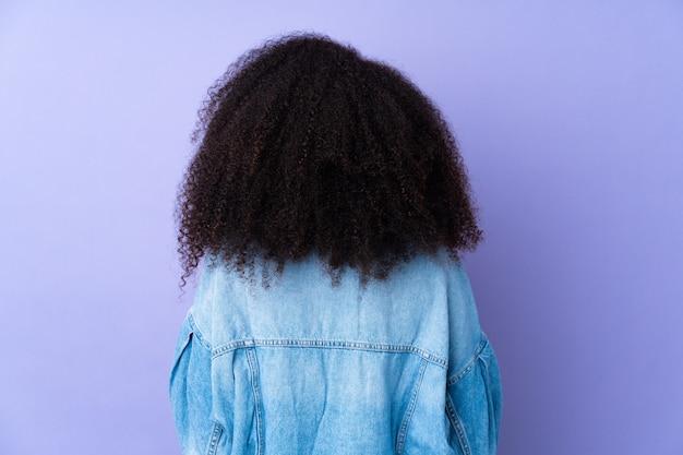 Jonge afro-amerikaanse vrouw geïsoleerd op paars in achterste positie