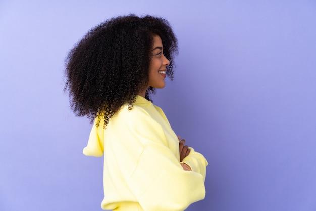 Jonge afro-amerikaanse vrouw geïsoleerd op paars in zijpositie