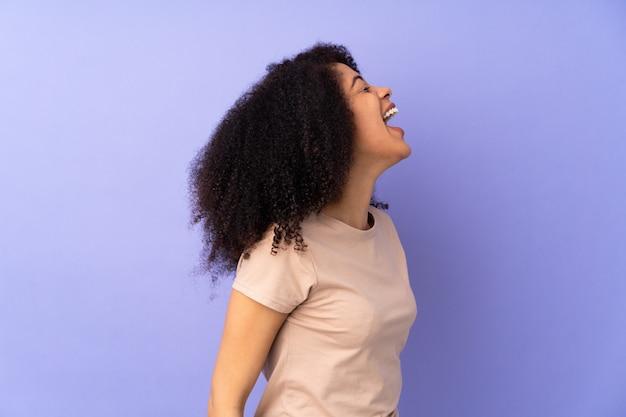 Jonge afro-amerikaanse vrouw geïsoleerd op paars lachen in zijligging