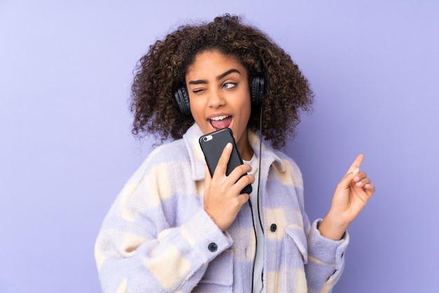 Jonge afro-amerikaanse vrouw geïsoleerd op paars luisteren muziek met een mobiel en zingen