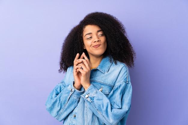 Jonge afro-amerikaanse vrouw geïsoleerd op paars plannen iets