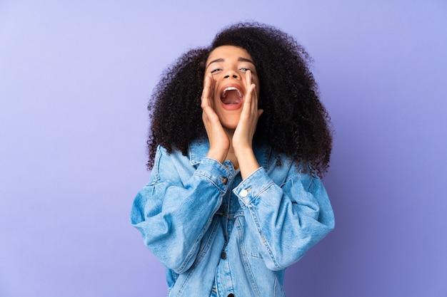 Jonge afro-amerikaanse vrouw geïsoleerd op paars schreeuwen en iets aankondigen