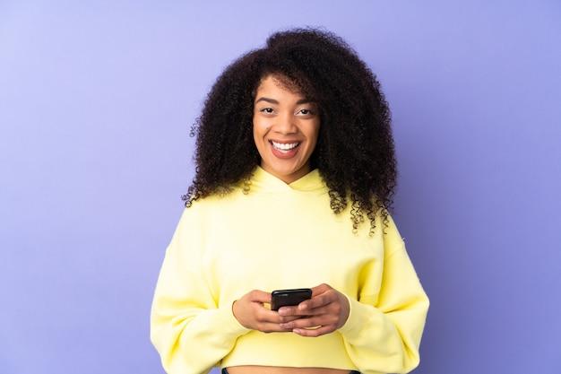 Jonge afro-amerikaanse vrouw geïsoleerd op paars verrast en een bericht verzenden