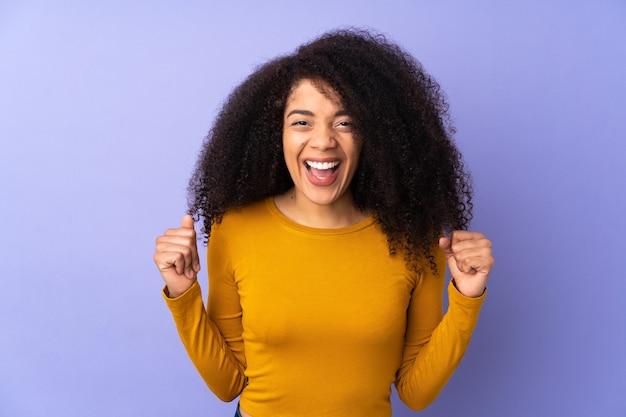 Jonge afro-amerikaanse vrouw geïsoleerd op paars vieren een overwinning in winnaarspositie