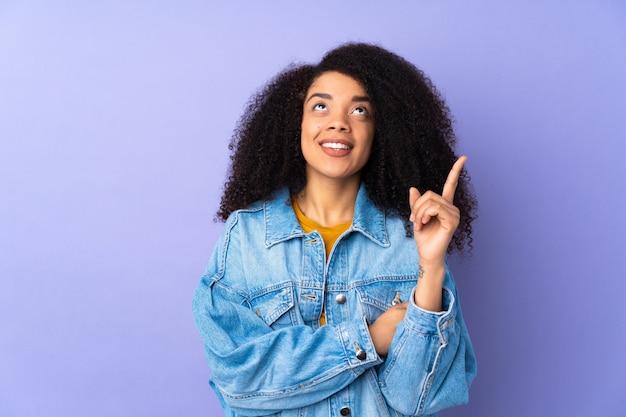 Jonge afro-amerikaanse vrouw geïsoleerd op paars wijst op een geweldig idee