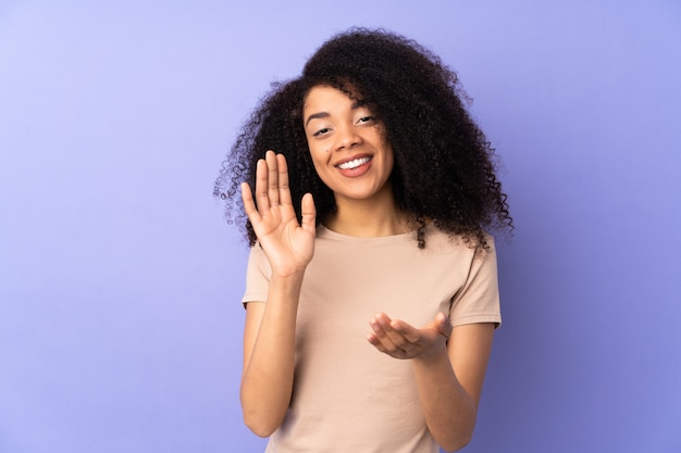 Jonge afro-amerikaanse vrouw geïsoleerd op paarse applaudisseren na presentatie in een conferentie