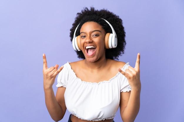 Jonge afro-amerikaanse vrouw geïsoleerd op paarse luisteren muziek rock gebaar maken