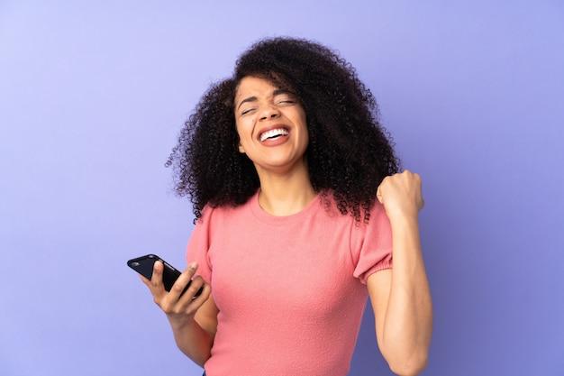 Jonge afro-amerikaanse vrouw geïsoleerd op paarse muur met telefoon in overwinningspositie